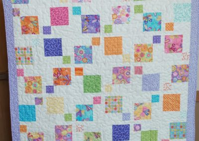 Shetek Camp Quilters – Diane, Holly, Linda & Pat - Sioux Falls SD Name - Twisted 9 Patch 48 ½ x56 Pieced and Machine Quilted Colors - Brite Pastels Charm quilt