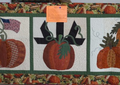 Shetek Camp Quilters – Diane, Holly, Linda & Pat - Sioux Falls SD Name – Pumpkin Patch 22x53 Pieced, Machine Quilted.  Appliqued by Judy Hines Colors - Orange, Creams, Yellow and Green