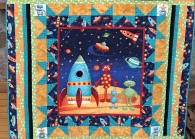 Diane, Holly, Linda & Pat – SF SD, Fun in Space, Pieced & machine quilted, 49x51, blue, gold, teal & red