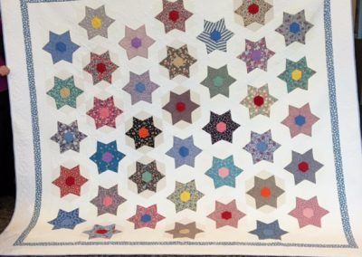 Peggy Ludeman – Tracy MN, Pieced & machine quilted, White with multi colored stars