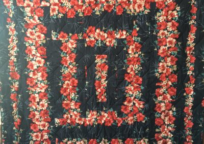 Lois Ahlschlager – Balaton MN, Hawaiian Hibiscus Garden, Pieced & machine quilted, Queen – black with red flowers materials purchased at Hilo Hatties in Hawaii