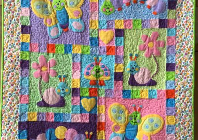 Lynn Larsen- Billings MT Name - Baby Bugs 45x54 Pieced, Appliqued and Machine Quilted Color - Pastel colors