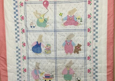 So Many Bunnies – 42x48 – Tied & embroidered - Pink, Blue & yellow – Made by Lucille Magnus – Slayton, MN