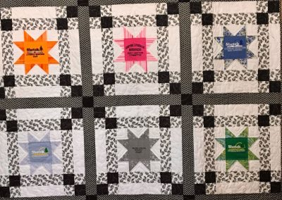 SLM Logo Stars – 53x70 – Pieced and Machine Quilted – Black & White W/SLM Shirt logos – Made by Lynn Larson- Billings, MT – The T-shirts in this quilt belonged to Lynn's Mother Bev Holland.  Bev was a SLM quilt committee member for 16 years.  Lynn made this quilt in honor and memory of her Mother.  Bev will be missed!
