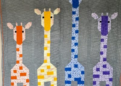 Giraffes in a Row- 38x38 – Pieced & Machine quilted – Orange, yellow, Blue, and Purple with gray background with orange back– Made by LaNan (Bliss) Eldrige – Primghar, Iowa