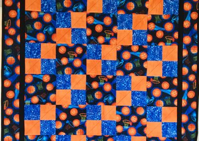 Basketballs – 38x44 – Pieced & machine quilted – orange, black, blue fleece back – Made by Jean Weness – Worthington, MN