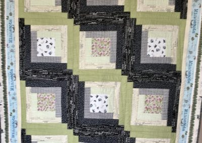 Minnesota Log Cabin – 50x67 – Pieced & Machine Quilted – Greys, greens & blues backed w/ grey plaid fleece – Made by Jean Weness – Worthington, MN