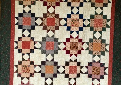 Maple Star – 58x70 – Pieced & Machine Quilted – Earth Tones – Donated by American Lutheran of Windom, MN  - Made by Jean Johnson – Windom, MN