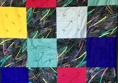 Bursts & Blocks – 58x80 – Pieced & Tied – Multi colored Blocks w/black back – Made by American Lutheran Quilters – Windom, MN