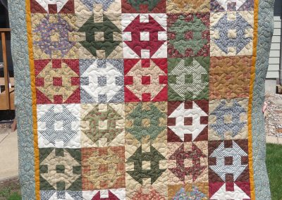 Thimble berries Churn Dash – 59 ½ x69 ½ - Pieced & machine Quilted – Earth tones/multi colors – Made by Diane, Holly, Linda & Pat – Sioux Falls, SD