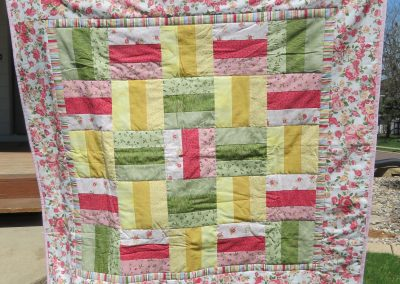 A Walk in the Garden – 42x42 – Pieced & Machine Quilted – Pinks, yellow, greens – Made by Eastside Lutheran Quilters – Sioux Falls, SD