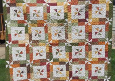 Pinwheels – 65x78 – Pieced & Machine Quilted – Brown, Rusts, Gold, Framed pinwheel w/pinwheel border – Made by Diane, Holly, Linda & Pat – Sioux Falls, SD