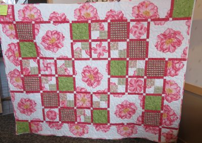 Pocket Full of Posies – 64x80 – Pieced & Machine Quilted – Rhubarb, green, cream – Made by Diane, Holly, Linda & Pat – Sioux Falls, SD